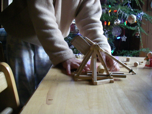 """Trebuchet02 shows the weapon in firing position. The taut string over the arm has a loop in the far side of this view, pegged by a """"key"""" made from a piece of coat hanger wire. She's about ready to pull that key, which will launch the cork piece (others of which you can see in the background)."""